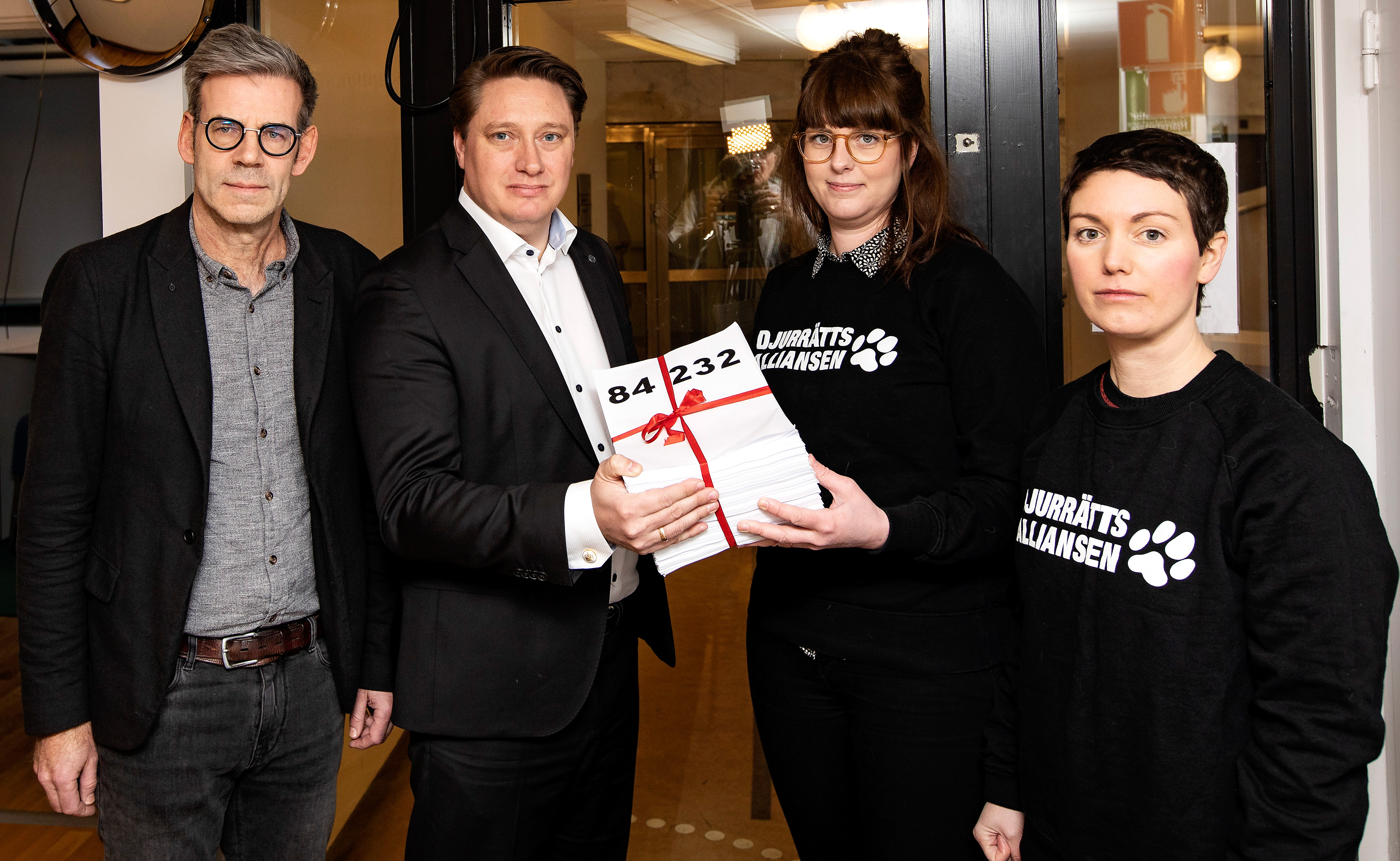 Göran Landberg and Mattias Goksör receive a petition from Malin Gustafsson and Emelie Wiberg of the Animal Rights Alliance.