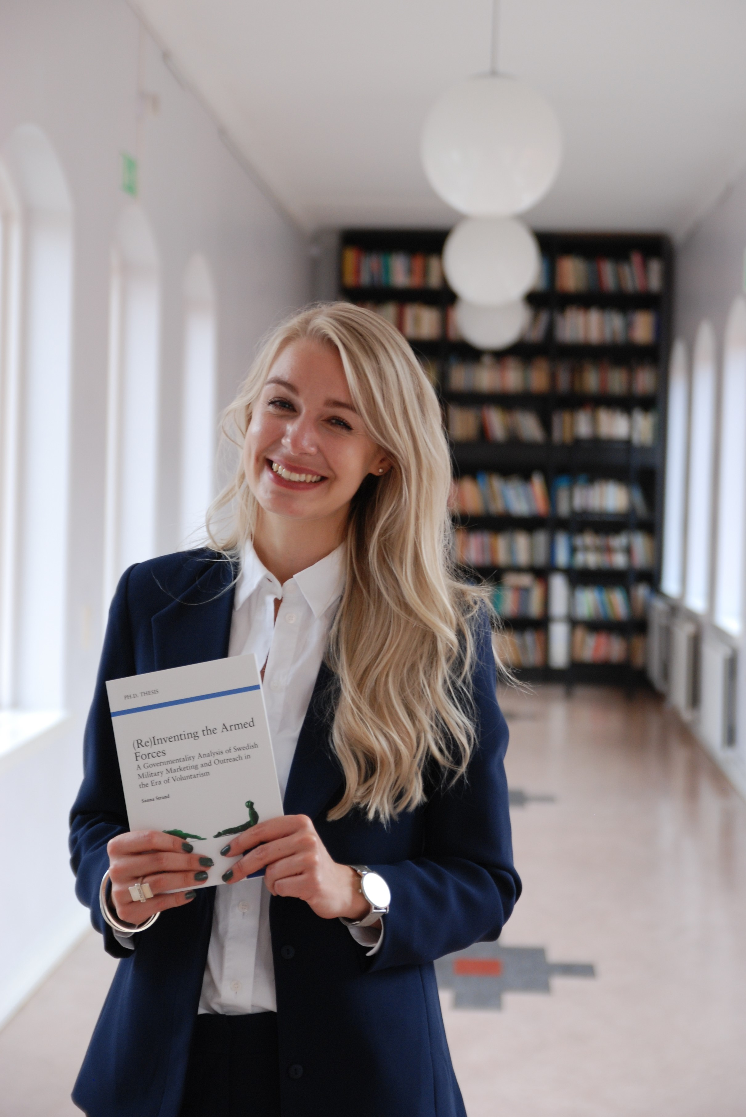 Sanna Strand with her PhD thesis (Re)Inventing the Armed Forces: A Governmentality Analysis of Swedish Military Marketing and Outreach in the Era of Voluntarism.