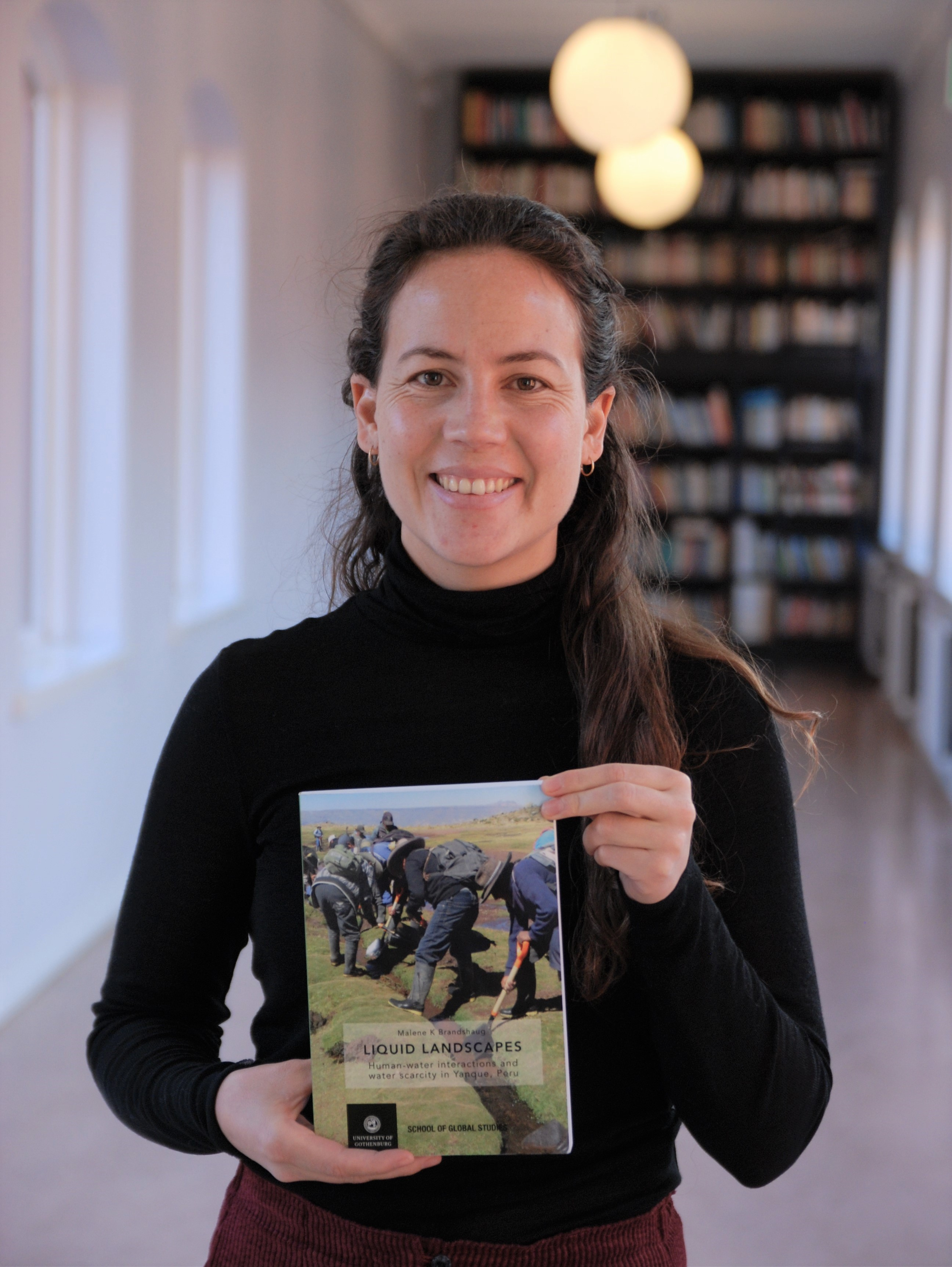 Malene K Brandshaug with her PhD thesis 'Liquid landscapes: Human-water interactions and water scarcity in Yanque, Peru