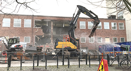 excavator demolishes buildning