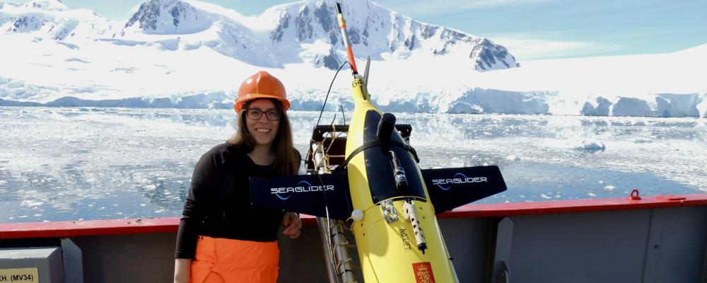 Researcher Louise Biddle with ocean glider Semla in front of an iceberg.