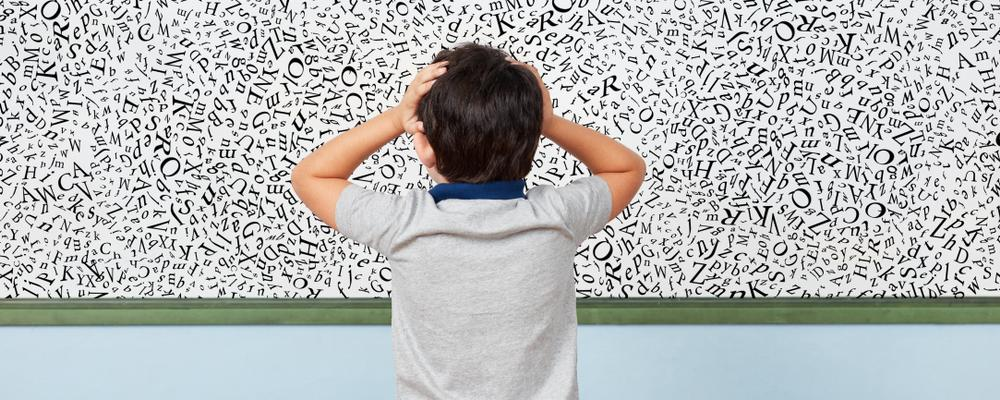 Child with dyslexia is standing in front of a whiteboard with many letters in elementary school