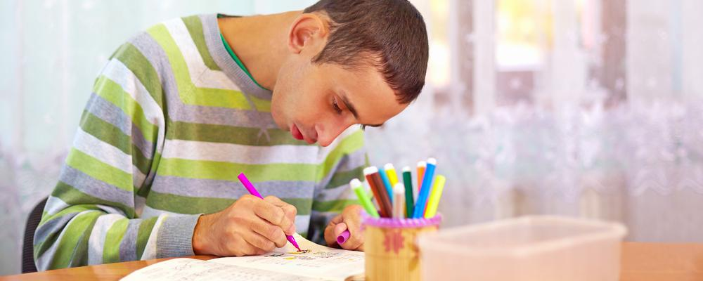 Man with intellectual disability at desk colouring and writing