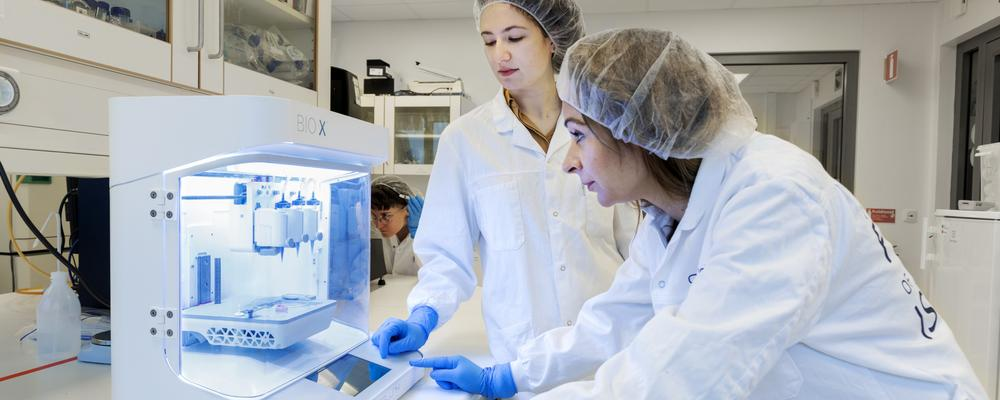 Three women working with a bioprinting machine