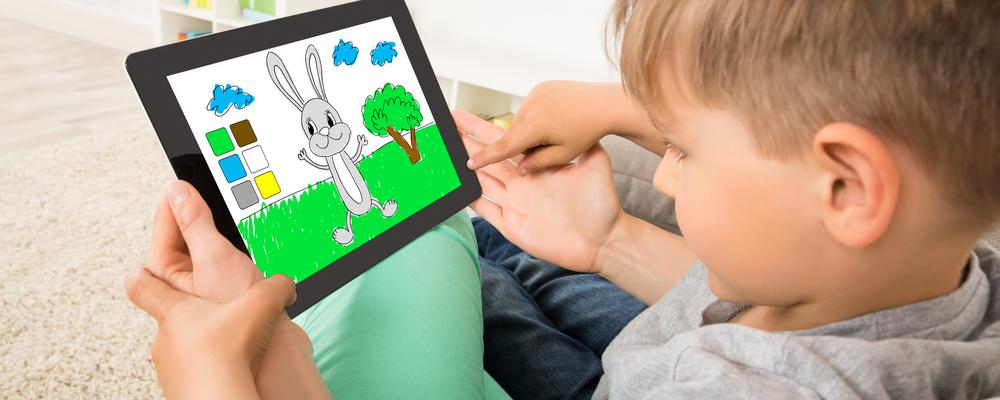 Close-up Of Little Boy Playing Game On Digital Tablet